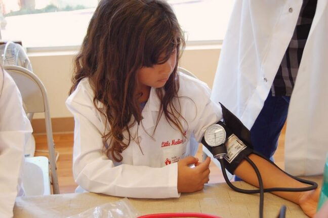 Little Medical School Ottawa. OpencityInc blog. Child using a blood pressure cuff.